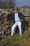 Farmer Portrait with Smile on Face. Smiling farmer posing for a portrait. He is working on stacking firewood for the winter and smiling for the camera royalty free stock photo