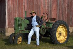 Farmer Poses With His Tractor. Farmer proudly showing off his Tractor stock photography