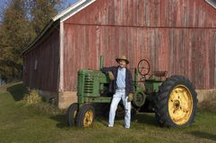 Farmer Poses With His Tractor. Farmer proudly showing off his Tractor royalty free stock photo