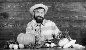 Farmer presenting hot chilli pepper wooden background. Man hold pepper harvest. Bearded farmer hold pepper in hand stock photos