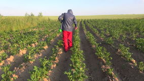 Farmer with protective equipment spraying potato field stock footage