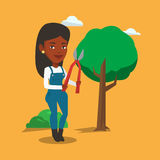 Farmer with pruner in garden vector illustration. An african-american gardener holding a pruner. Gardener is going to trim branches of a tree using pruner Royalty Free Stock Photography