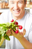 Farmer with radish in farm shop Stock Photography