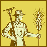 Farmer With Rake and Wheat Woodcut. Illustration of a farmer worker holding a rake and wheat set inside square done in retro woodcut style royalty free illustration