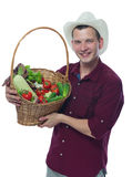 Farmer in a red shirt holding a basket of vegetables Royalty Free Stock Photos