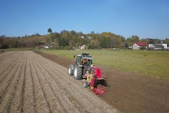 A farmer on a red tractor with a seeder sows grain in plowed land in a private field in the village area. Mechanization of spring. Field work. Farmer`s everyday stock photos
