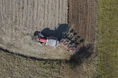 A farmer on a red tractor with a seeder sows grain in plowed land in a private field in the village area. Mechanization of spring. Field work. Farmer`s everyday stock photo