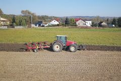 A farmer on a red tractor with a seeder sows grain in plowed land in a private field in the village area. Mechanization of spring. Field work. Farmer`s everyday royalty free stock photos
