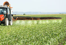Farmer in red tractor spraying soybean field royalty free stock photo
