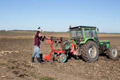 Farmer repairing tractor Stock Photo