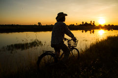 Farmer riding bicycle Stock Photos