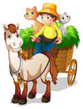A farmer riding in a strawcart with his farm animals Royalty Free Stock Photography