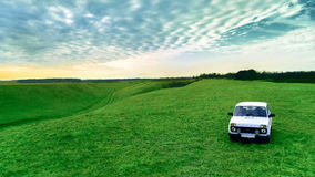 Farmer`s car and green field against the sky. Russian rural landscape Royalty Free Stock Images