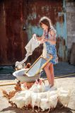 The farmer`s daughter is washing his father`s shirt in the yard.  Royalty Free Stock Image