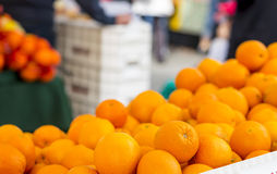 Farmer's Market Oranges. A pile of fresh oranges at a farmer's market in San Francisco. Shoppers out of focus in the background royalty free stock photo