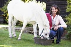 Farmer's Wife Feeding Pony Stock Photography