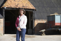 Farmer's Wife Standing In Front Of Farm Buildings Stock Photography