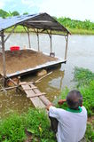 A farmer is sad looking at his pangsius catfish farm in the mekong delta of Vietnam. Pangasius is stuck in the US market because o. AN GIANG, VIETNAM - AUGUST 25 Stock Photo