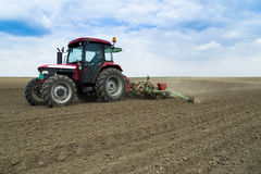 Farmer seeding corn crops at field with pneumatic seeder. stock photo