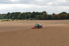 Farmer seeding crops at field. In spring Stock Photos