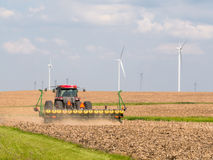 Farmer seeding next to wind farm Royalty Free Stock Photography