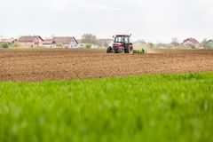 Farmer seeding, sowing crops at field. Sowing is the process of planting seeds in the ground as part of the early spring time agricultural activities Stock Photos