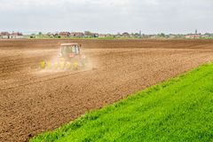 Farmer seeding, sowing crops at field. Sowing is the process of planting seeds in the ground as part of the early spring time agricultural activities Stock Photo