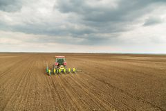 Farmer seeding, sowing crops at field. Sowing is the process of planting seeds in the ground as part of the early spring time agricultural activities Royalty Free Stock Photos
