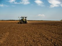 Farmer seeding, sowing crops at field. Sowing is the process of planting seeds in the ground as part of the early spring time agricultural activities Royalty Free Stock Images