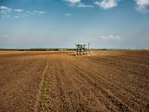 Farmer seeding, sowing crops at field. Sowing is the process of planting seeds in the ground as part of the early spring time agricultural activities Royalty Free Stock Photography
