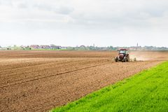 Farmer seeding, sowing crops at field. Sowing is the process of planting seeds in the ground as part of the early spring time agricultural activities Stock Image