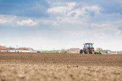 Farmer seeding, sowing crops at field. Sowing is the process of planting seeds in the ground as part of the early spring time agri. Cultural activities Royalty Free Stock Images
