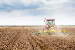 Farmer seeding, sowing crops at field. Sowing is the process of planting seeds in the ground as part of the early spring time agri. Cultural activities Royalty Free Stock Photo