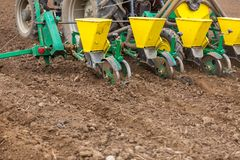 Farmer seeding, sowing crops at field. Sowing is the process of planting seeds in the ground as part of the early spring time agri. Cultural activities Stock Images