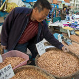 A farmer selling peanuts. A farmer was selling his newly harvested peanuts at a morning market, northeast China, satisfied with the current price which was Royalty Free Stock Photo