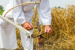 Farmer is sharpening, ironing, repair the blade on scythe. Royalty Free Stock Photo