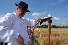 Farmer sharpening the scythe Stock Photo