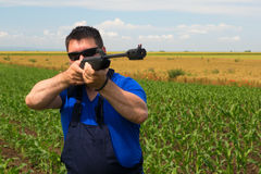 Farmer is shooting  with air gun in the corn field Stock Photo