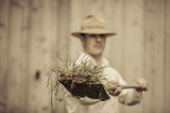 Farmer with a Shovel Full of Grass Stock Image