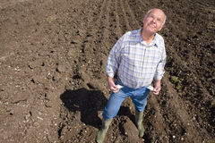 Farmer showing empty pockets and looking up in ploughed field Stock Photos