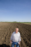 Farmer showing empty pockets in ploughed field Stock Photo
