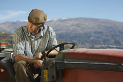 Farmer Sitting On Tractor Against Mountain. Middle age farmer sitting on tractor against mountain Stock Image