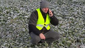 Farmer with smartphone on frozen field stock footage