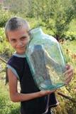 The farmer son. The boy  bears the big glass jar Royalty Free Stock Image