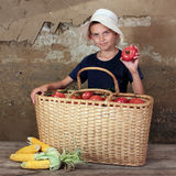 The farmer son. The boy in a white hatshows the repared crop a tomatoes Stock Photo