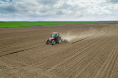 Farmer sowing crops at field with tractor Stock Photography