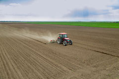 Farmer sowing crops at field with tractor Royalty Free Stock Photography