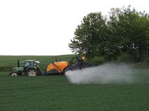 Farmer spraying chemicals in the fields. Near a wood in France royalty free stock image