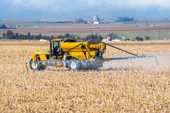 Farmer Spraying Fertilizer. Onto his field before plowing stock image
