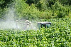 Farmer spraying grape vines. With tractor stock photos